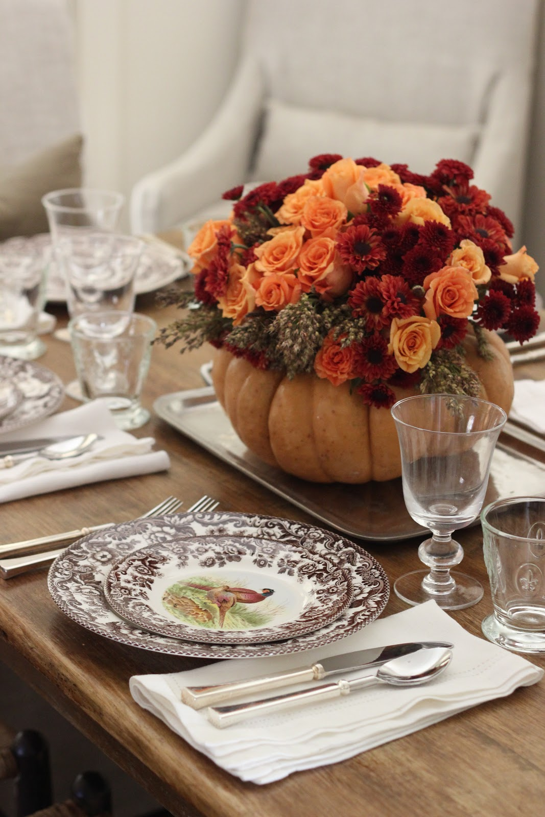 Roses, mums and broomsticks in a pumpkin vase