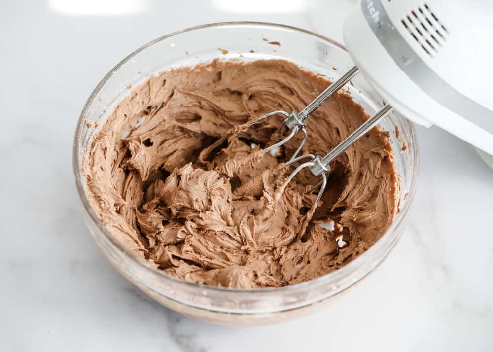 Mixing icing chocolate butter cream in a glass bowl