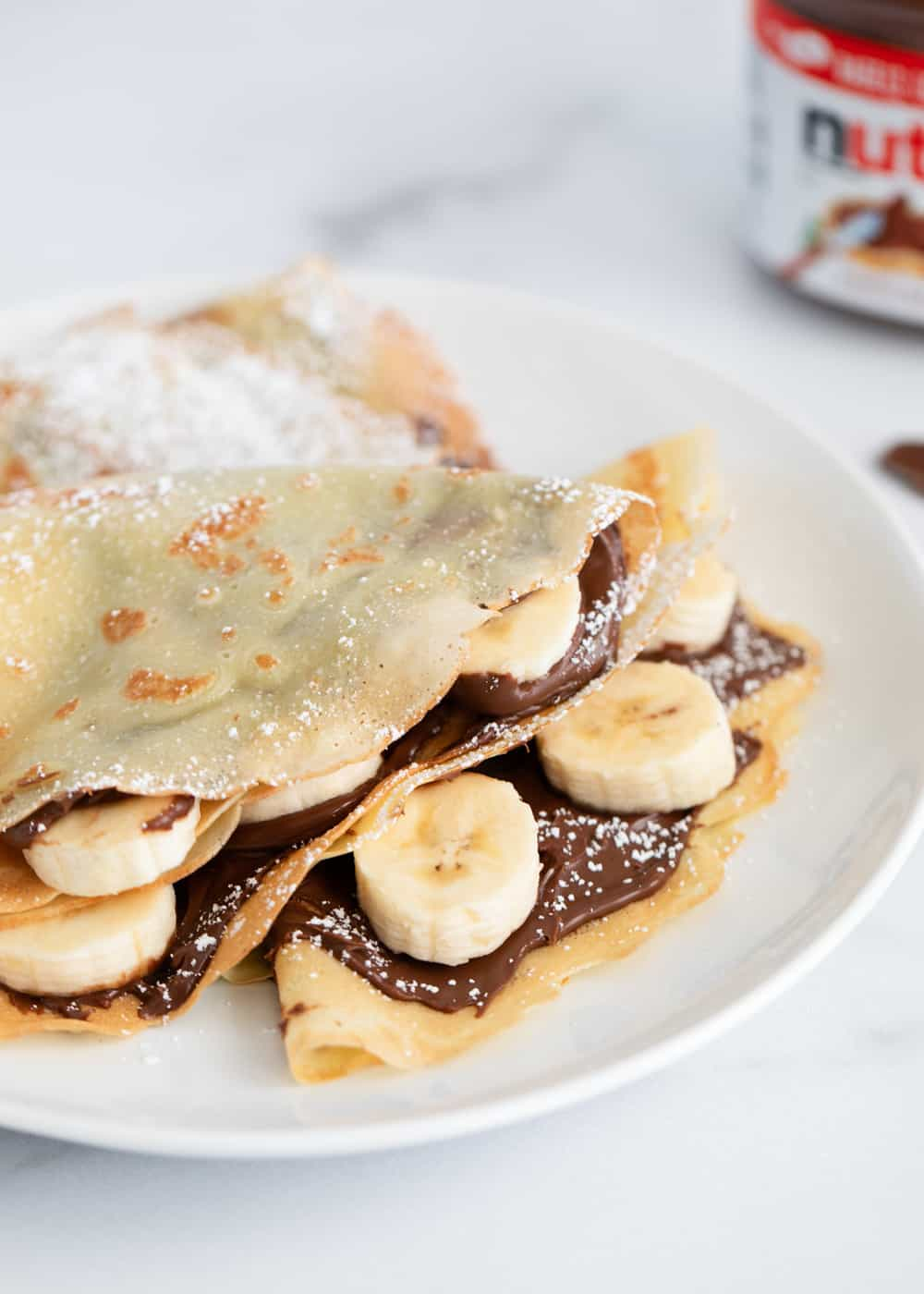Nutella pancakes with banana on white plate