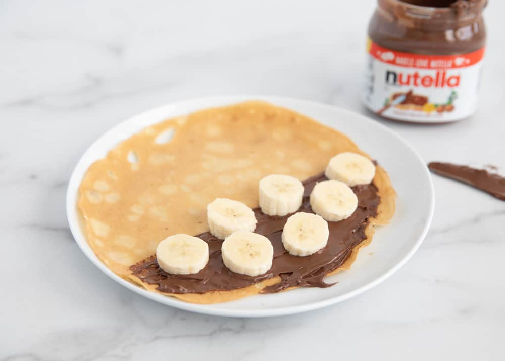 Nutella and banana are spread on a pancake