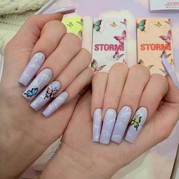 Purple nails with clouds and butterflies