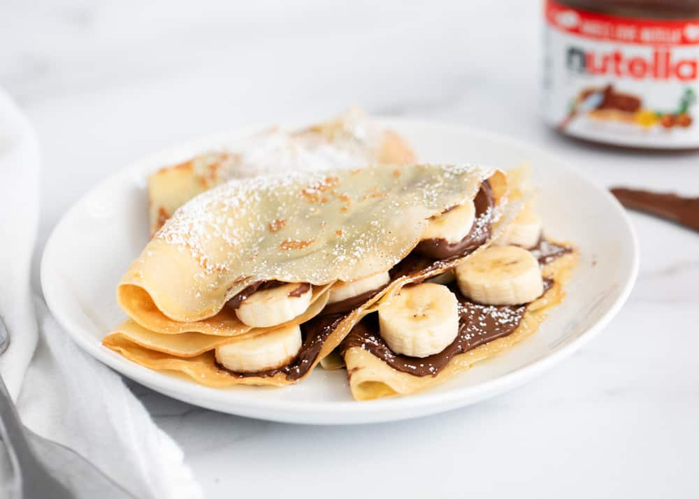 Banana Nutella pancakes on a white plate