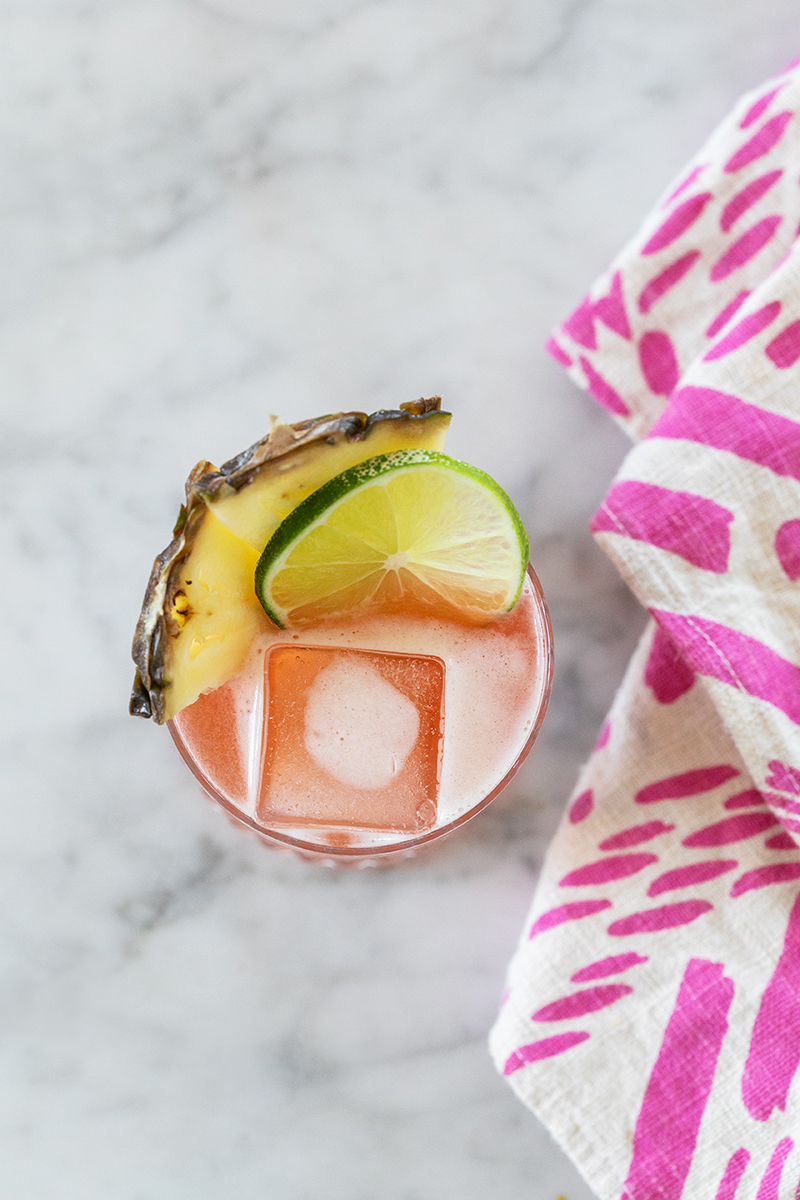 Overhead photo of a forest bird cocktail decorated with lime and pineapple and pink napkin.