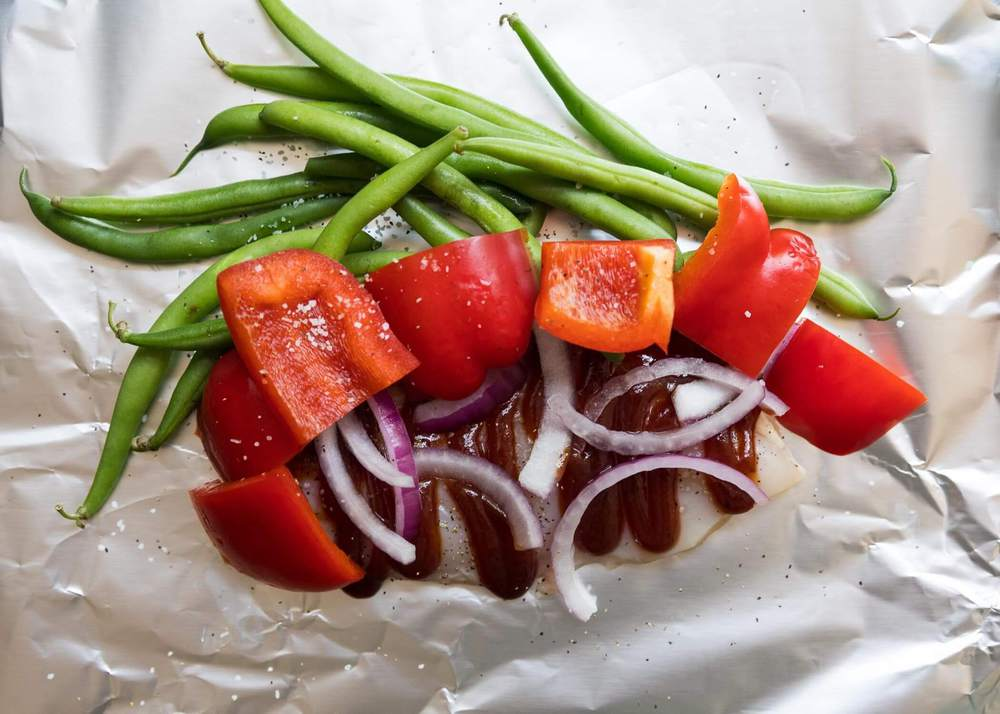 BBQ sauce and vegetables layered on foil