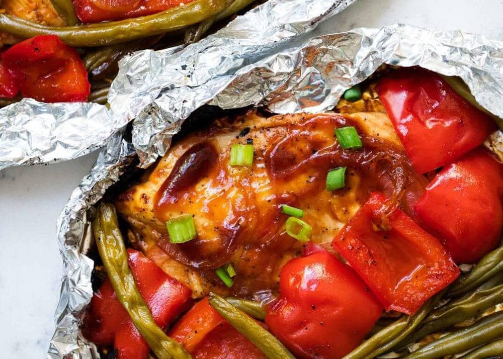 Grilled grilled chicken in a foil pack with vegetables