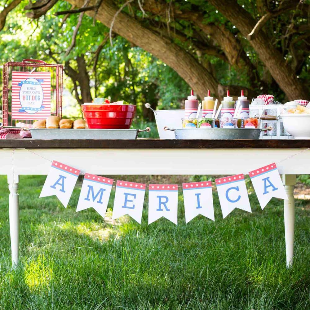 a table with an America banner hanging on a hot dog bar