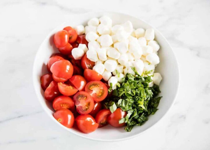 tomatoes, basil and mozzarella in white bowl