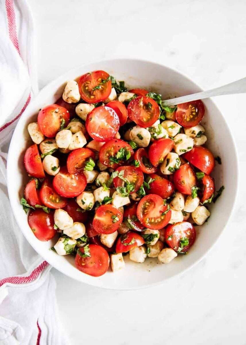 caprese salad in white bowl with spoon