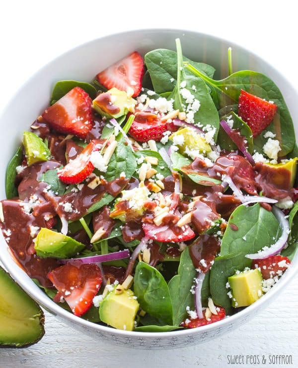 bowl of strawberry spinach salad with vinaigrette poured over it