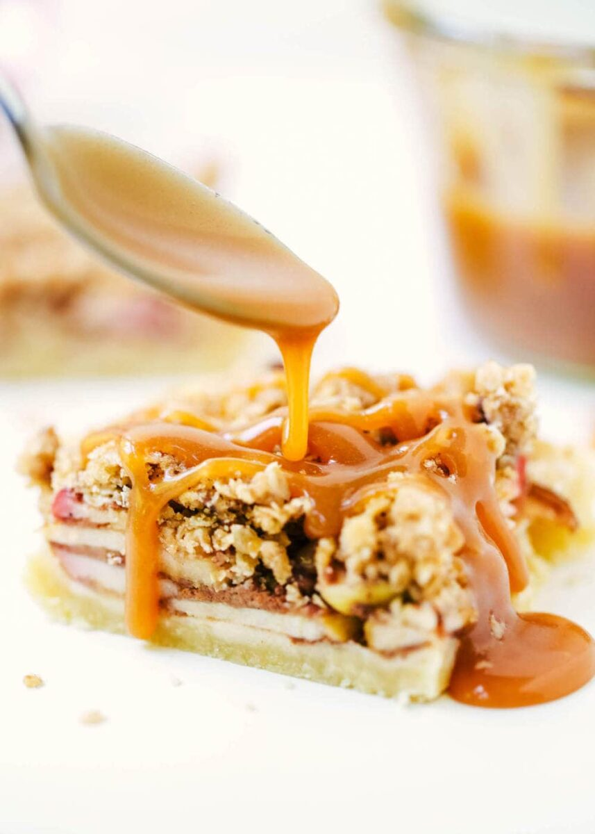 drizzling caramel over an apple pie bar with a spoon