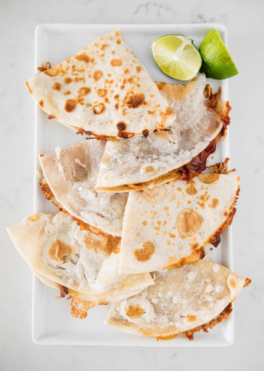 bbq pork quesadillas on a plate with a lime