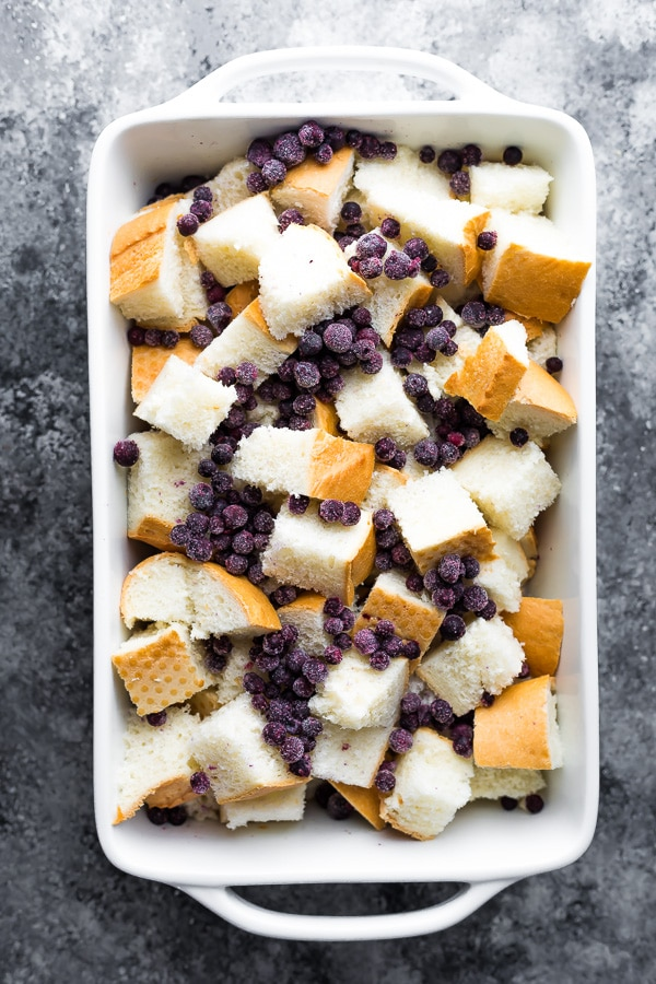 bread and blueberries in a baking dish for the Blueberry Overnight French Toast casserole