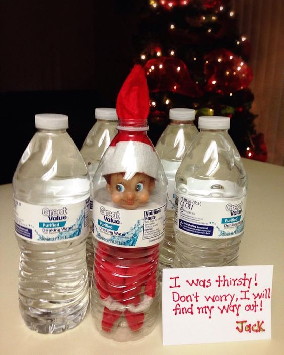 Funny Elf on the shelf stuck in a water bottle