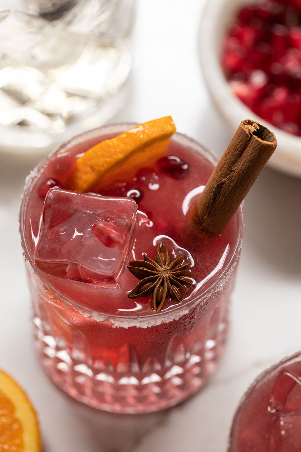 Red pomegranate margaritas with cinnamon stick, orange slice and star anise.