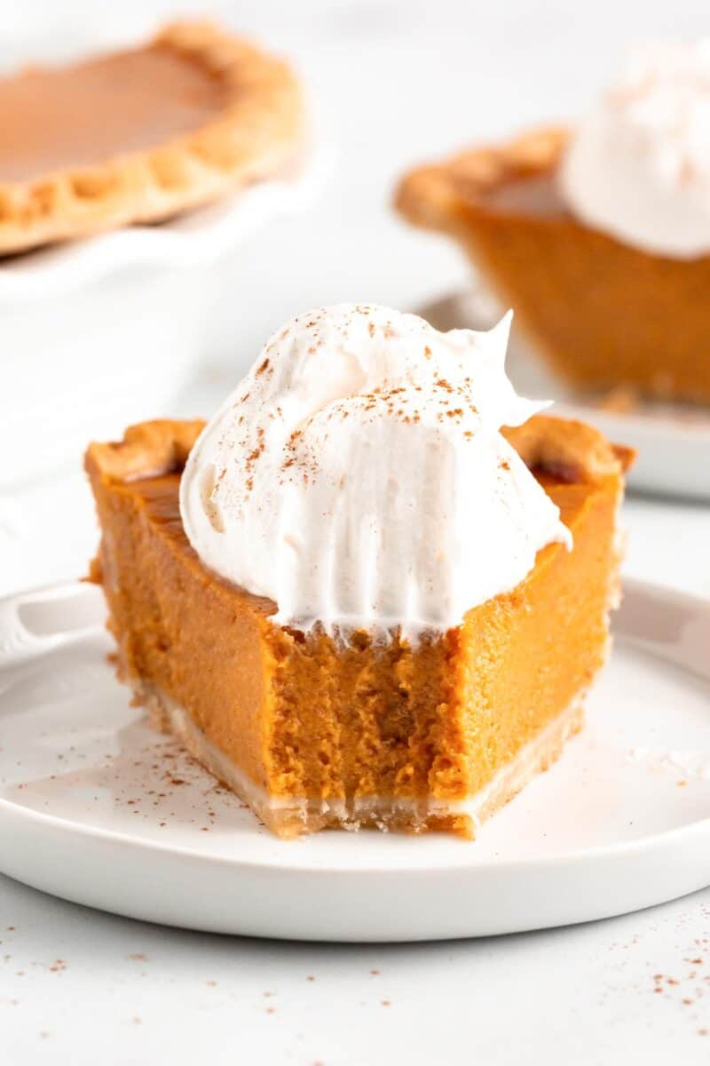 pumpkin pie with whipped cream on white plate