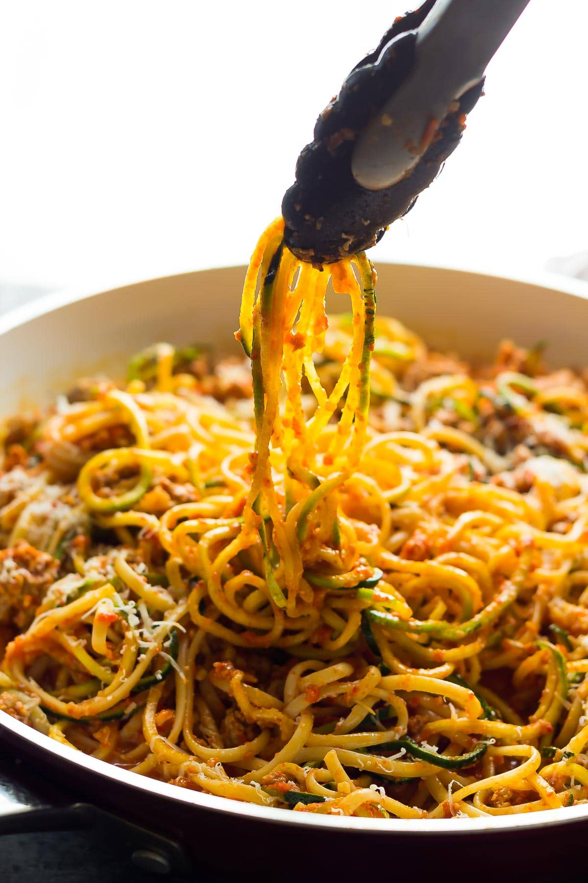 tongs pulling zucchini noodles in romesco sauce out of pan