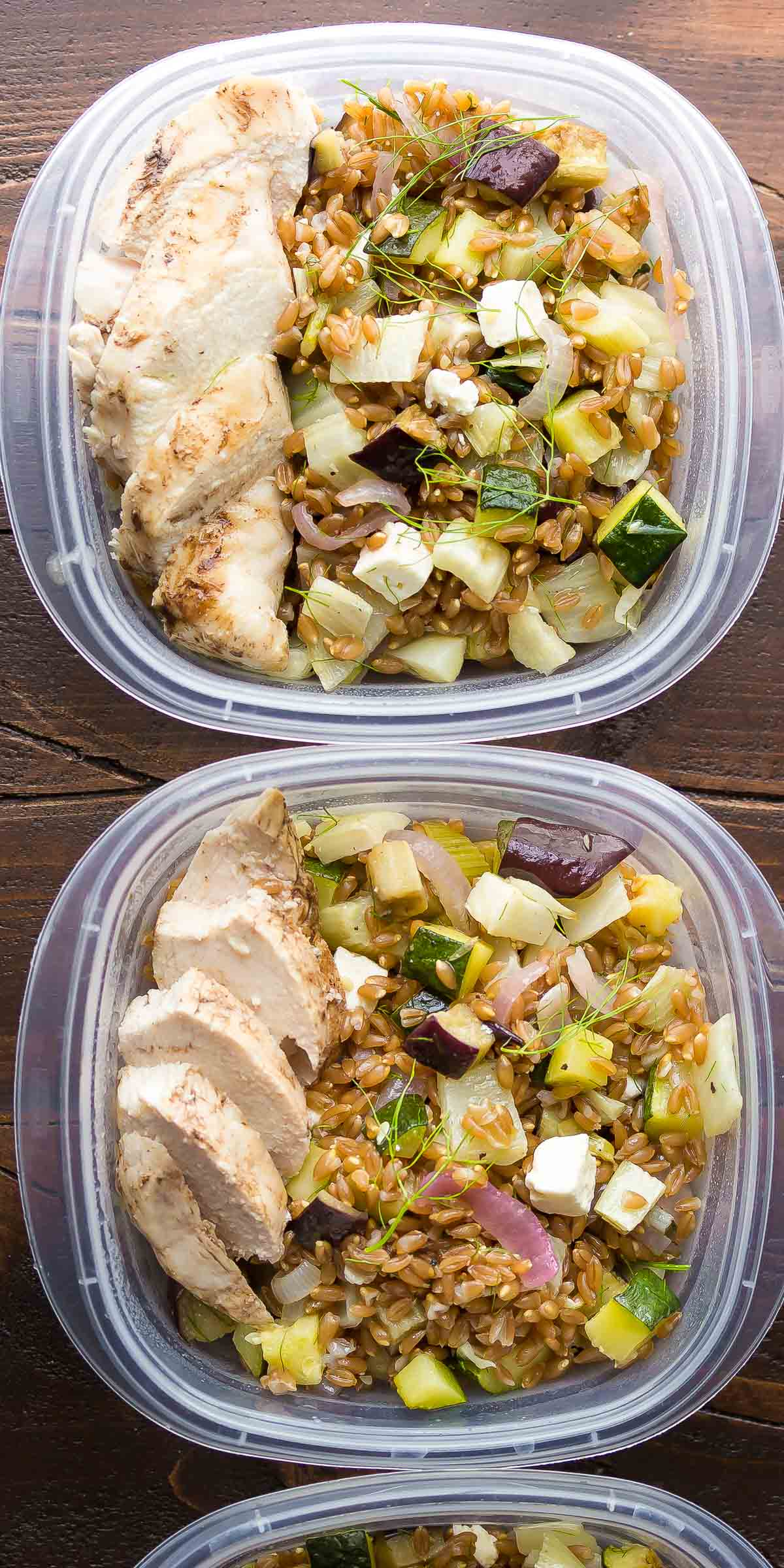 two meal prep containers with the mediterranean farro chicken lunch bowls