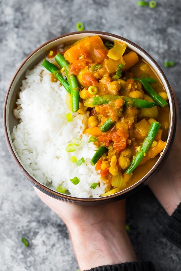 Hands are holding a bowl of chickpea curry cooked in a pre-made saucepan