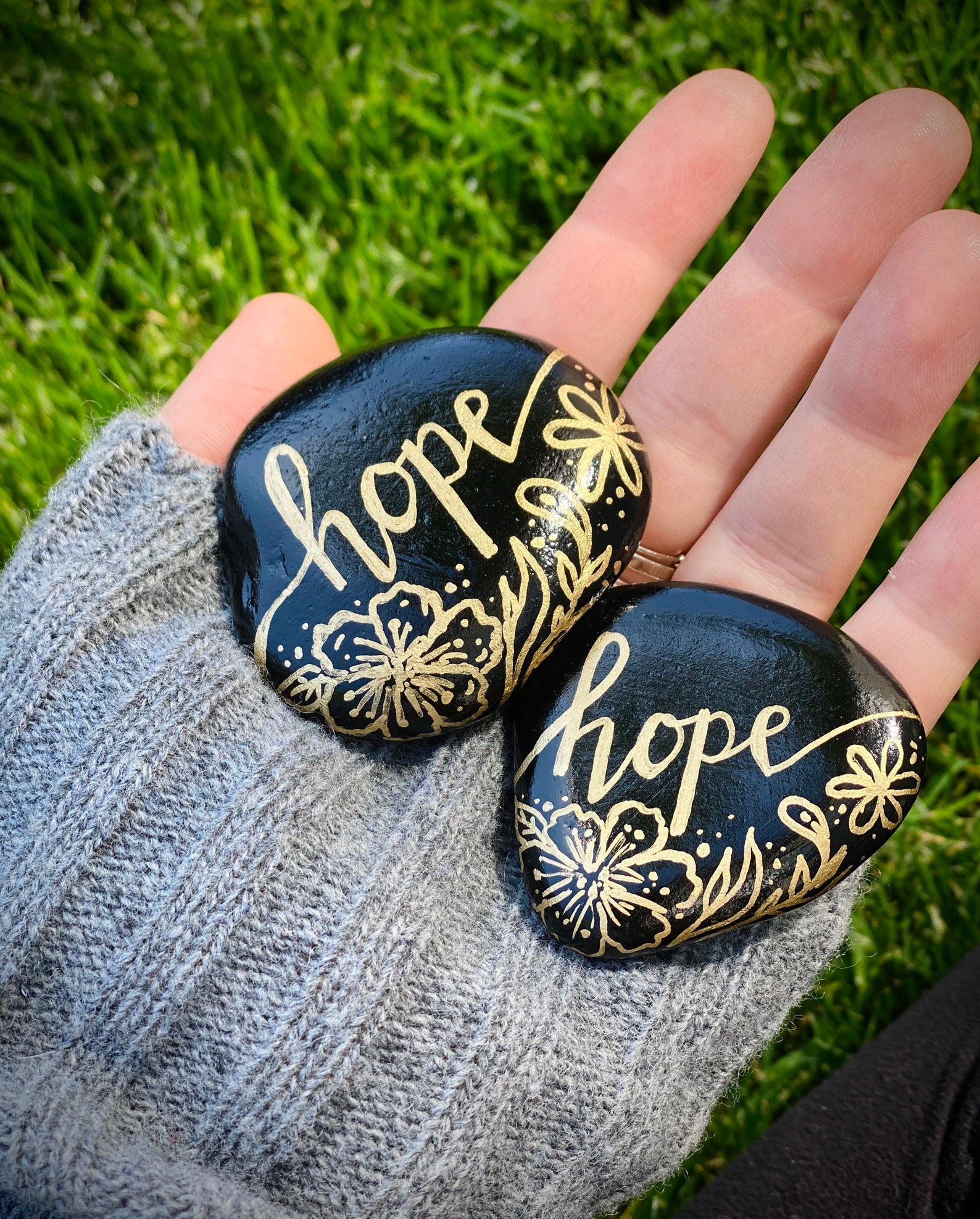 Black and gold painted rocks with quote