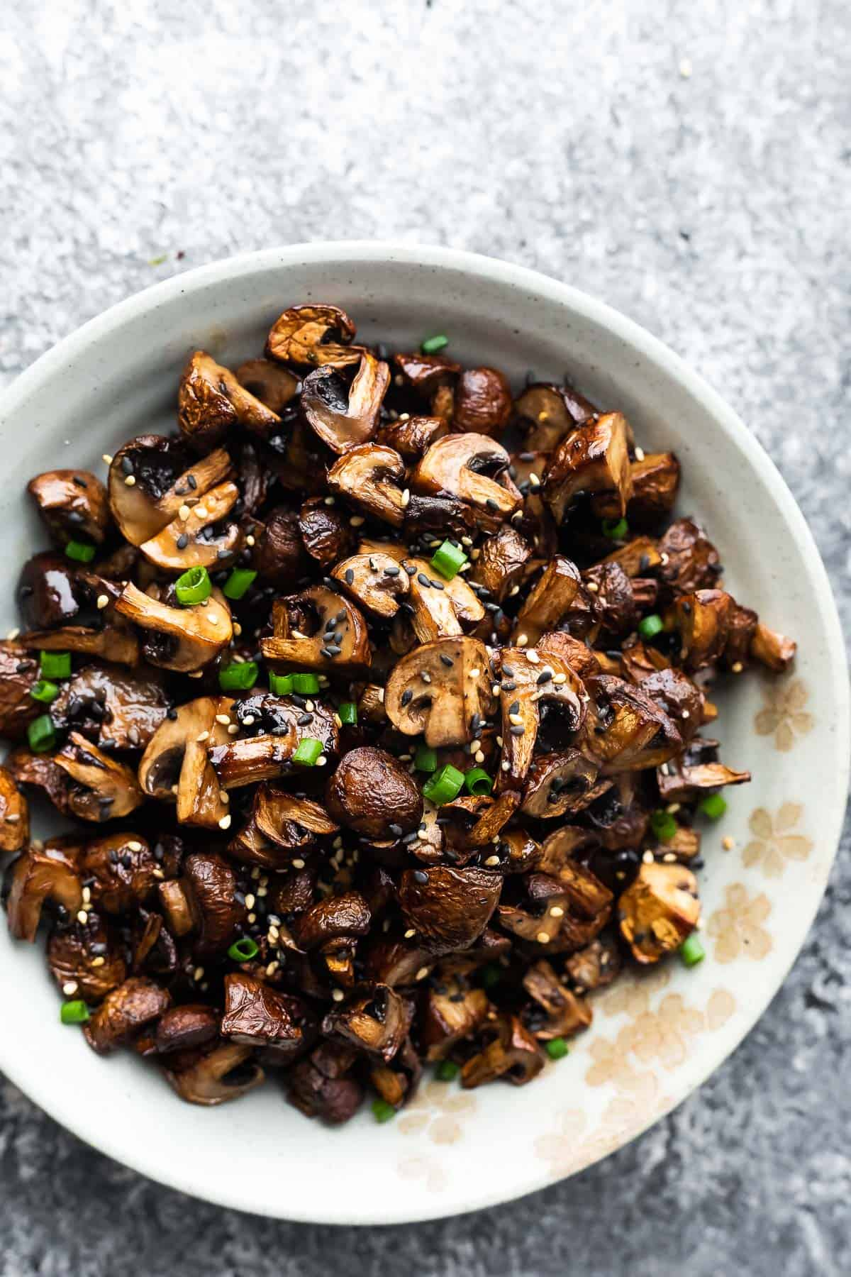 Air fryer mushrooms in a bowl with sesame seeds and green onions