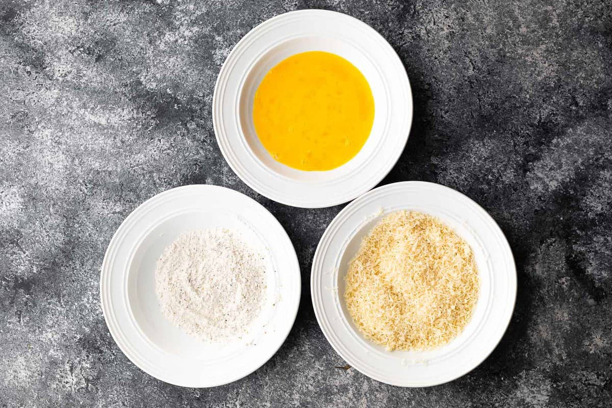 three bowls with flour, eggs and panko