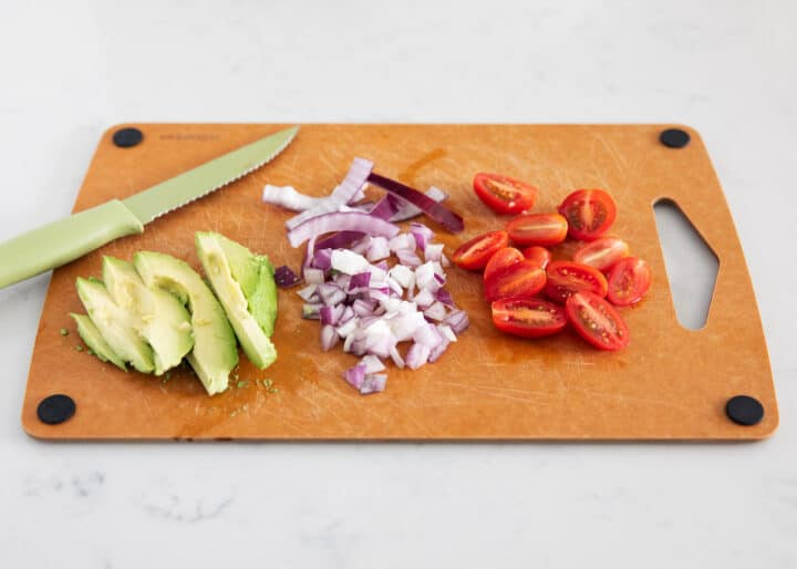 Avocado, red onion and tomato chopped on a cutting board