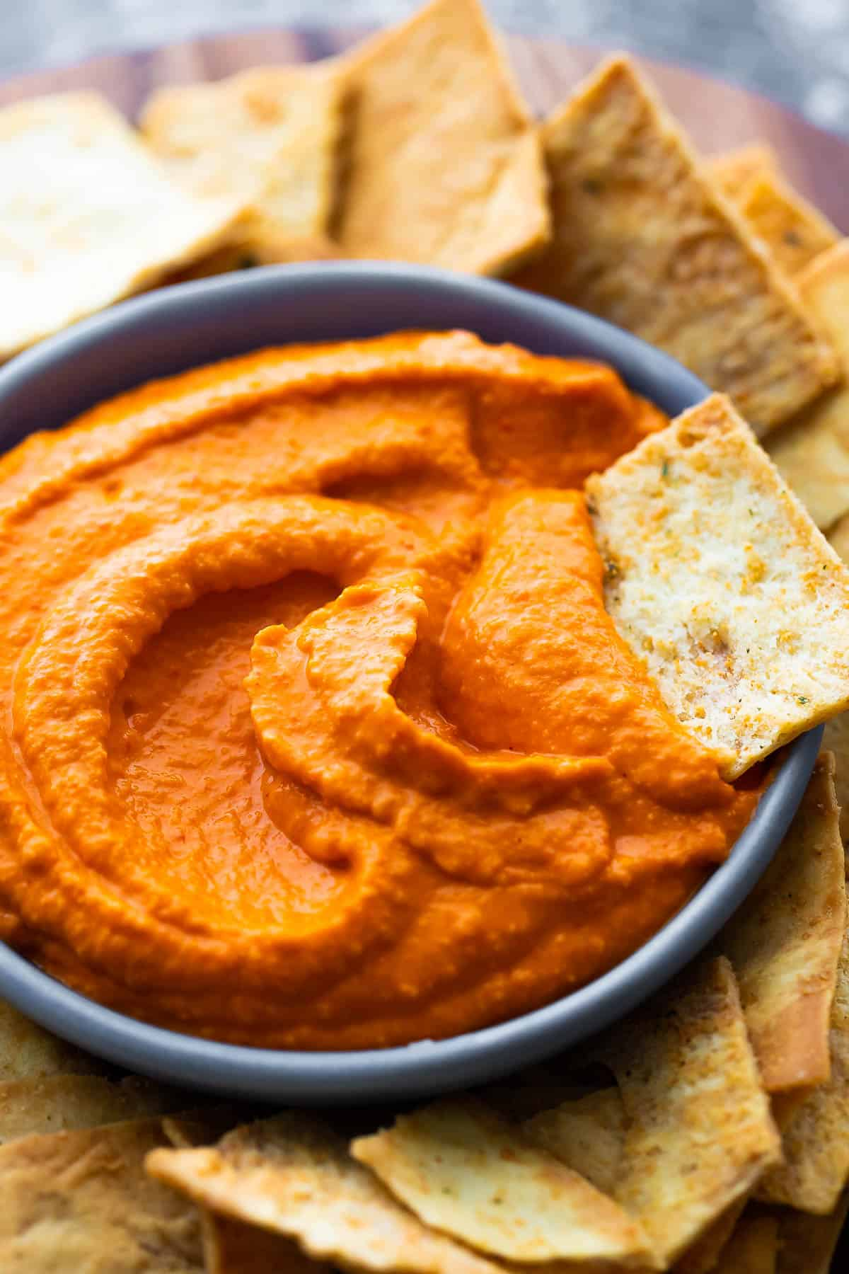 Close up of roasted red pepper hummus with pita chips