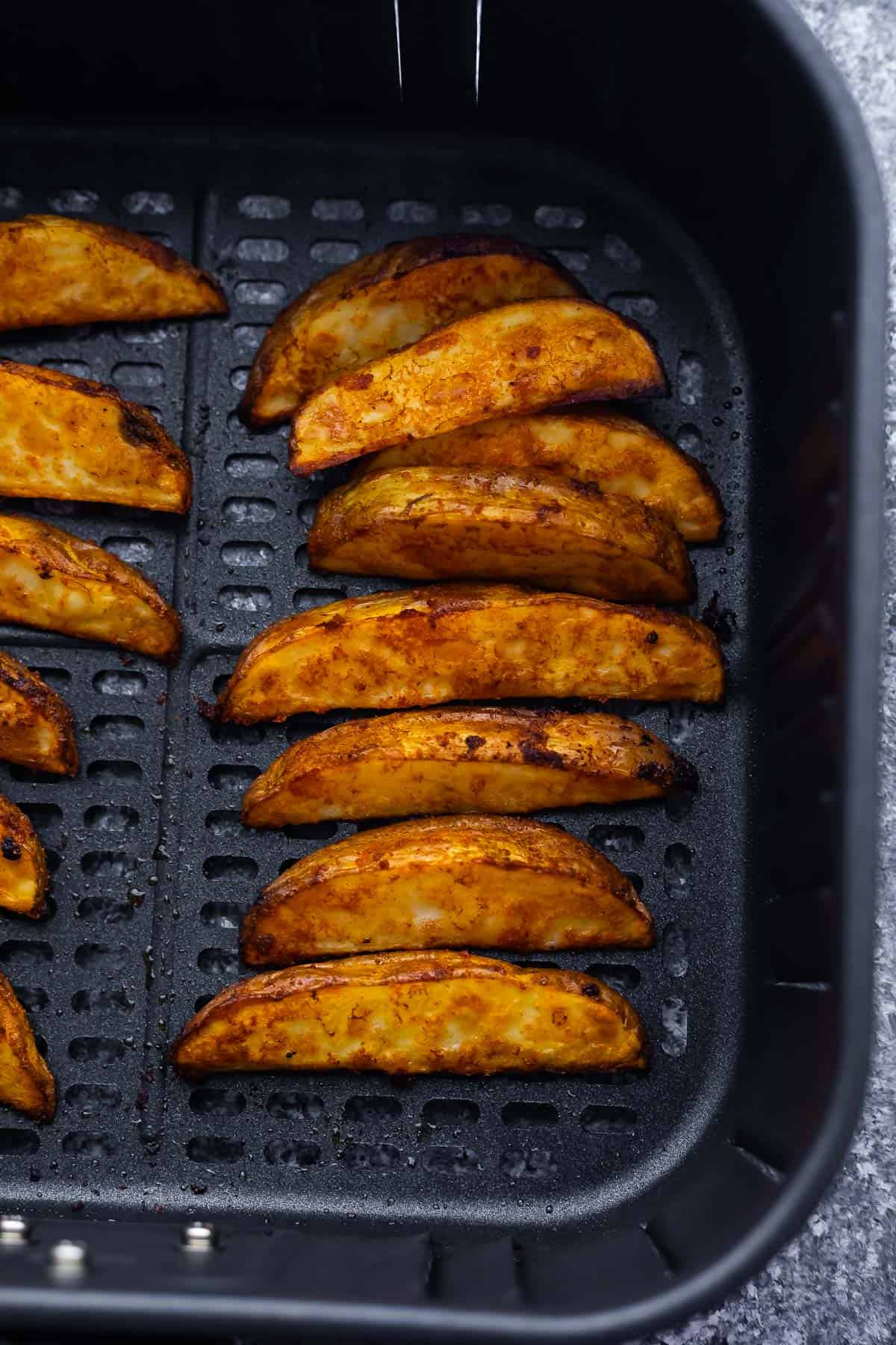 Baked potato wedges arranged in the frying basket