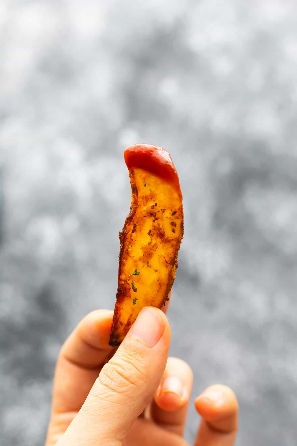 Hand holds potato wedges dipped in ketchup