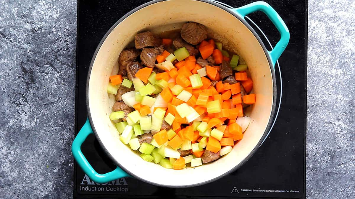 Onion, celery and carrot are added to the beef in a saucepan