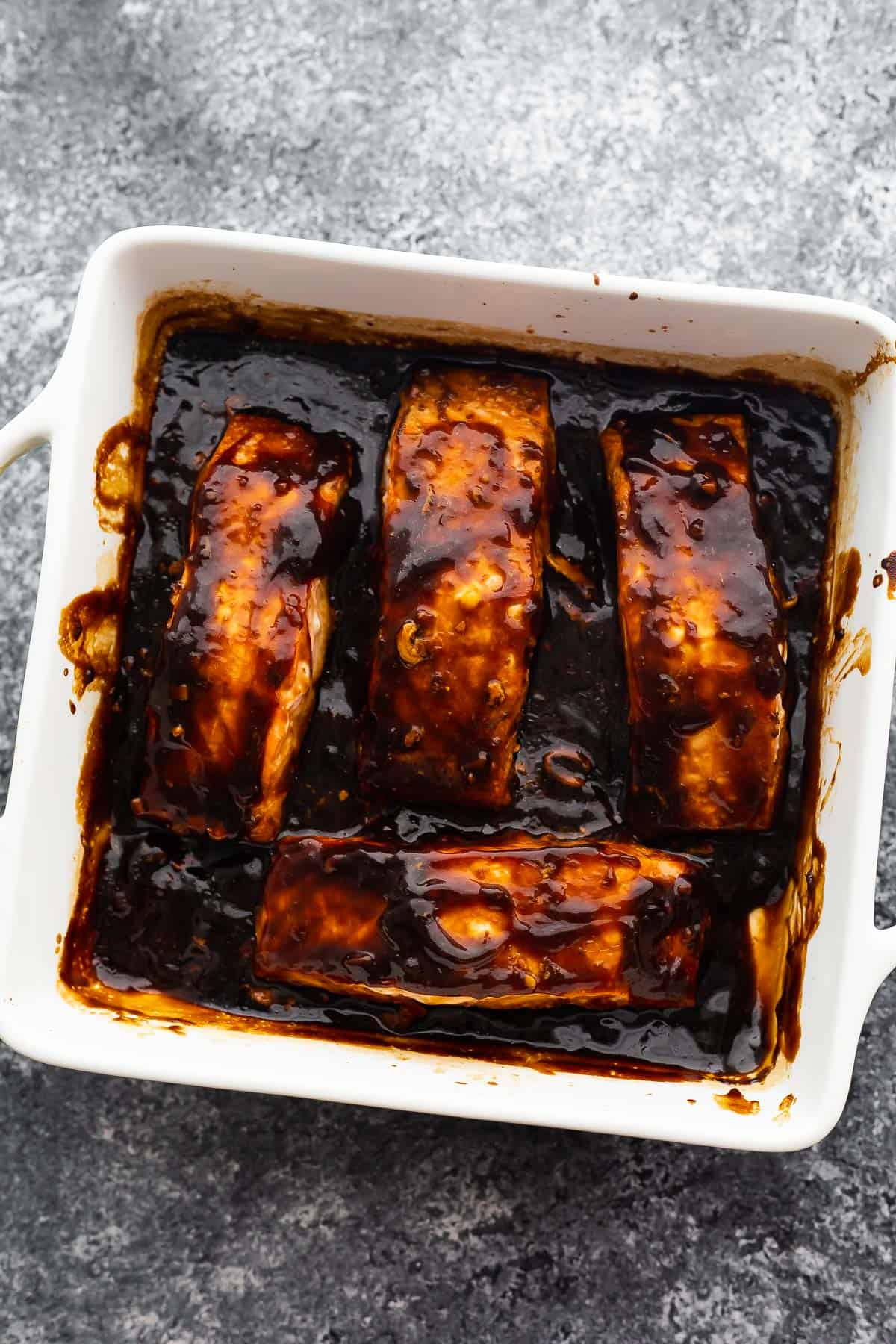 four baked salmon fillets on a baking sheet with thickened teriyaki sauce