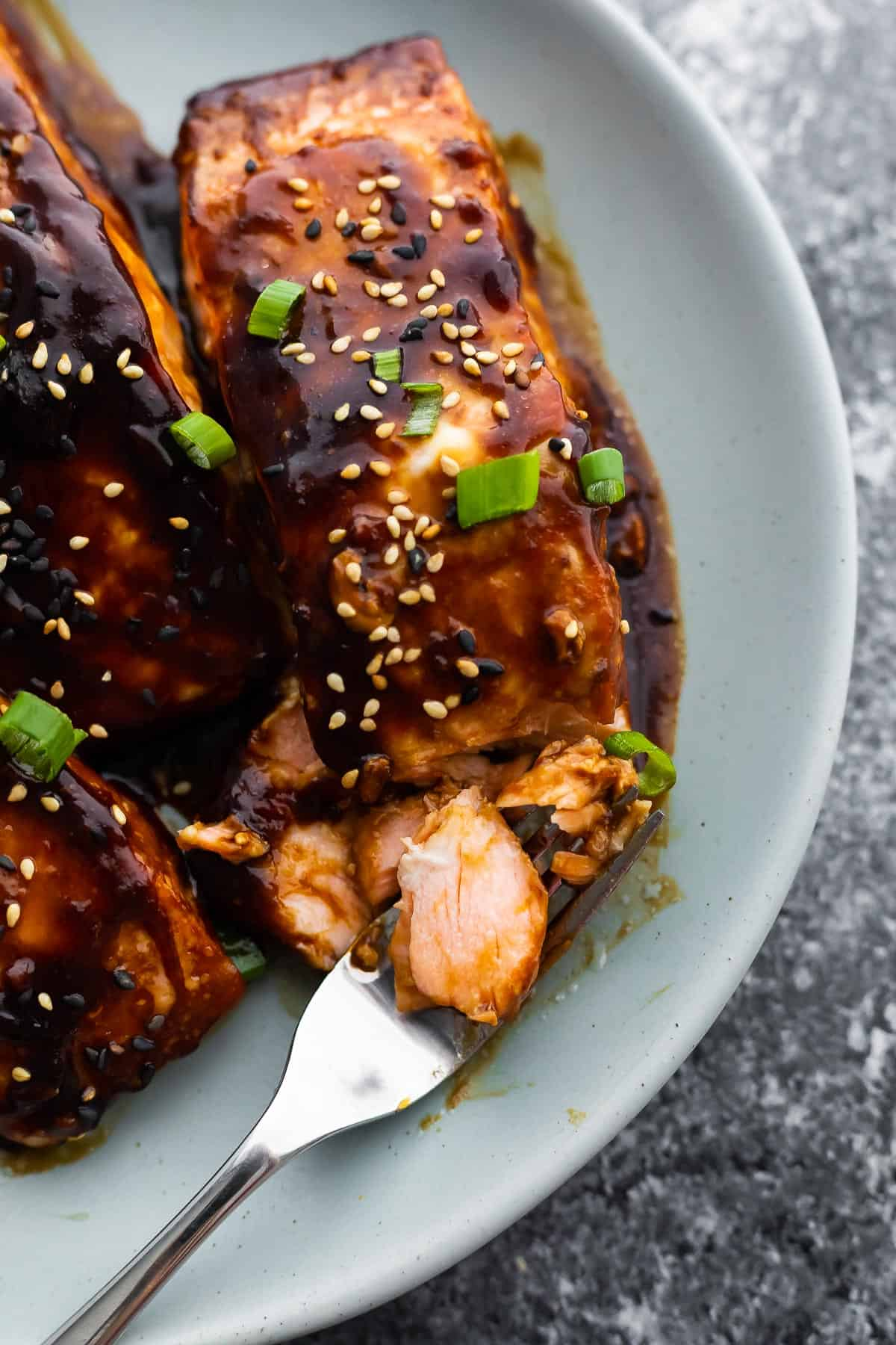 Close up of the teriyaki glazed salmon on the plate shown in the fork salmon
