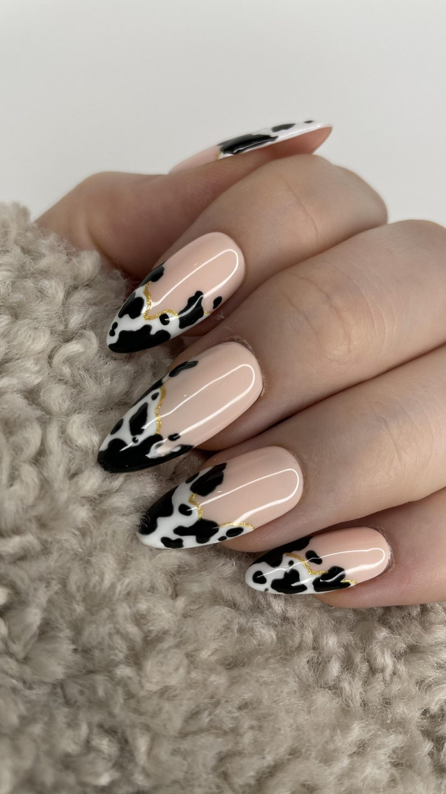 Nails with a cow patterned pink lacquer with a French tip