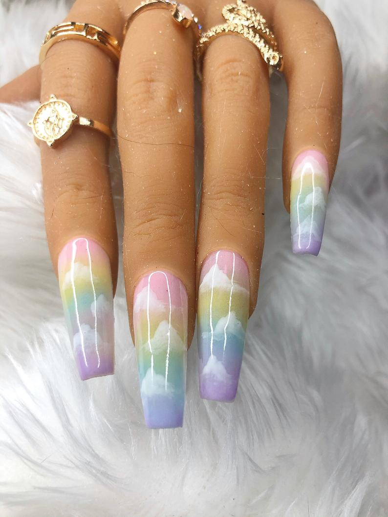 Cute pastel nails with a pastel rainbow ombre design and clouds