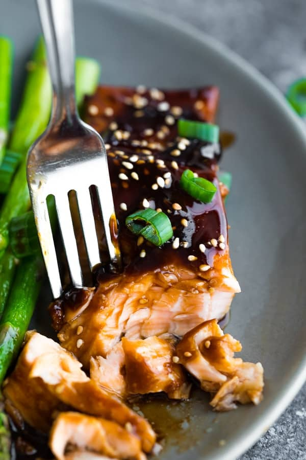 Close up of a fork peeling off the teriyaki salmon icing