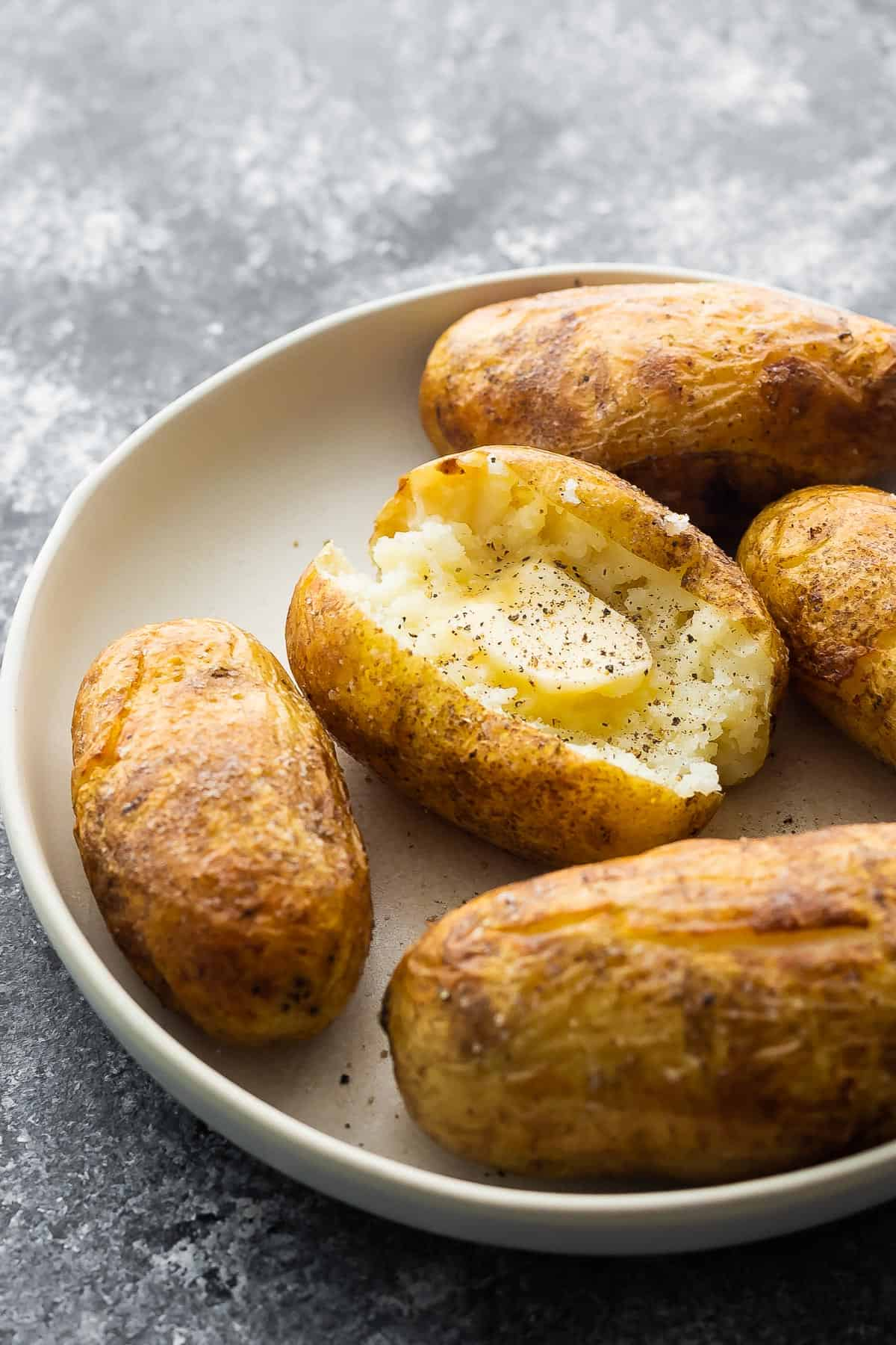 Baked potatoes in a ready-made saucepan with melted butter and black pepper