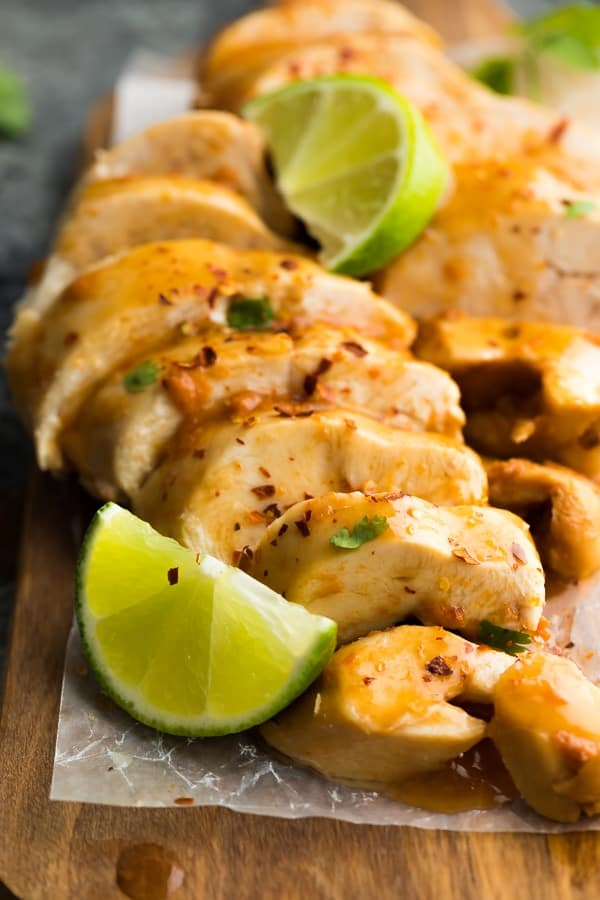 Close up of sliced chipotle lime chicken breast with lemon wedges on parchment paper