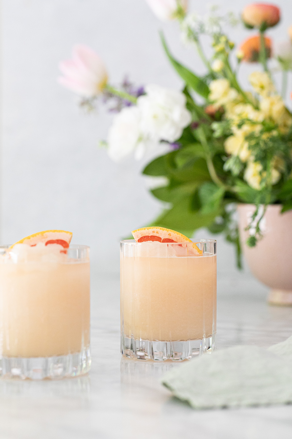Frozen Paloma cocktail in a glass with flowers behind it