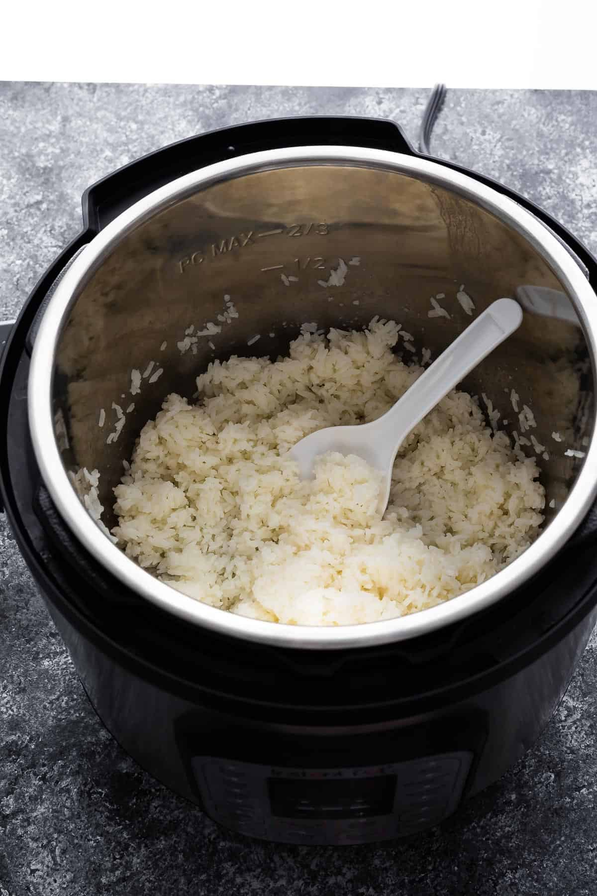 cooked jasmine rice in the finished pot with rice paddle