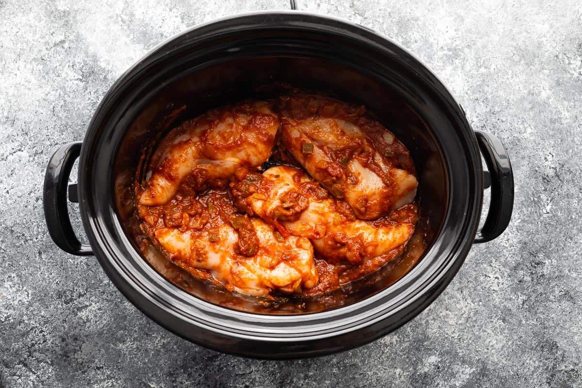 uncooked salsa chicken in a slow cooker