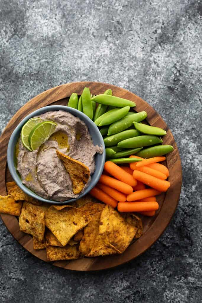Overhead view of a plate of carrots, peas, pita chips, and black bean hummus