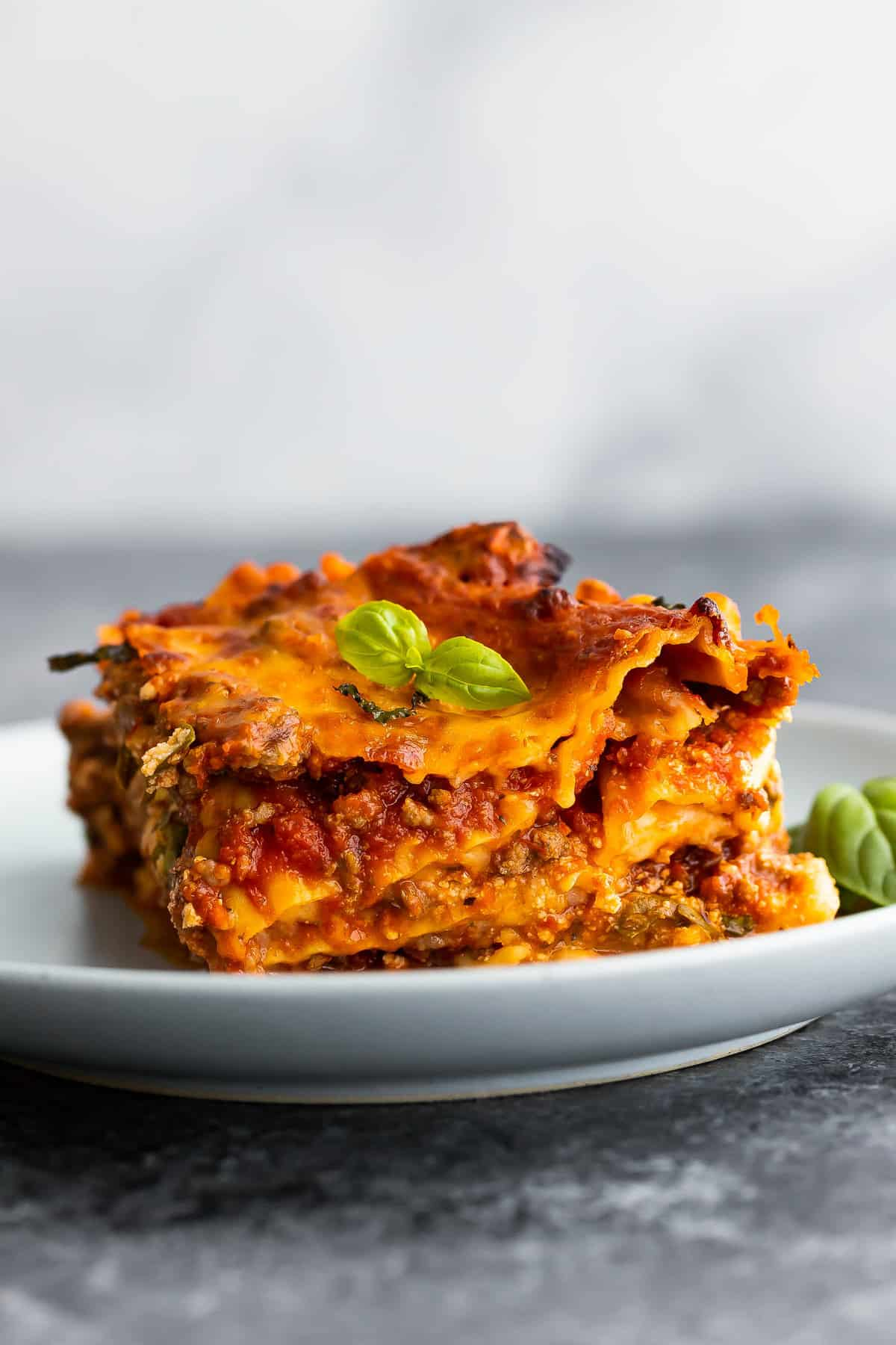 Side view of lasagne slice on plate with basil