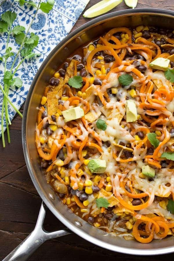 Overhead view of a pan of enchilada sweet potato noodles in a large pan on the table