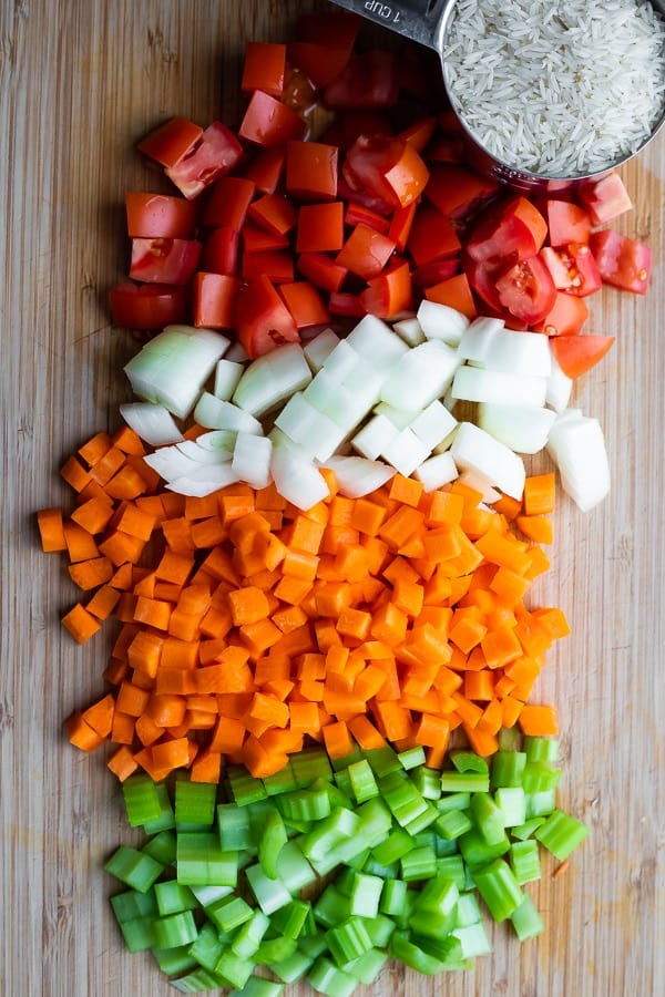 chopped tomatoes, onions, carrots and celery on a cutting board