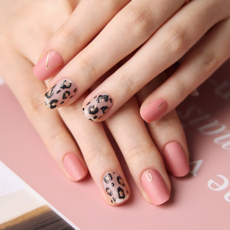 Delicate pink leopard nails with a gold pattern