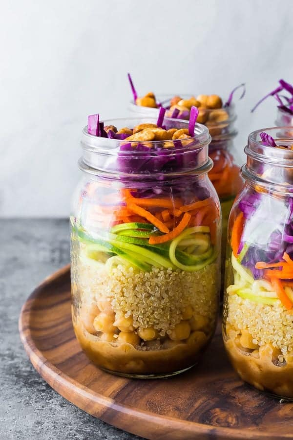 Close up of mason jars filled with Thai chickpea salad on wooden tray.