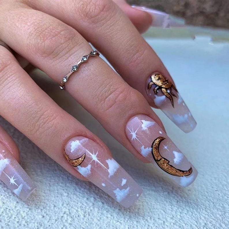 Transparent cloud nails with a golden crescent moon and sun